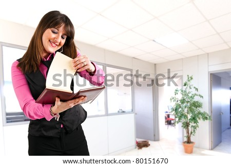 Woman accounting on her agenda while at the phone in her office - stock photo