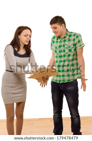 Woman accusing her boyfriend of wrongdoing pointing to a handful of papers in anger as he shrugs in ignorance, isolated on white - stock photo