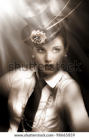 Woman actress in vaudeville costume of top-hat and tie standing lit up and illuminated under the bright lights of broadway - stock photo