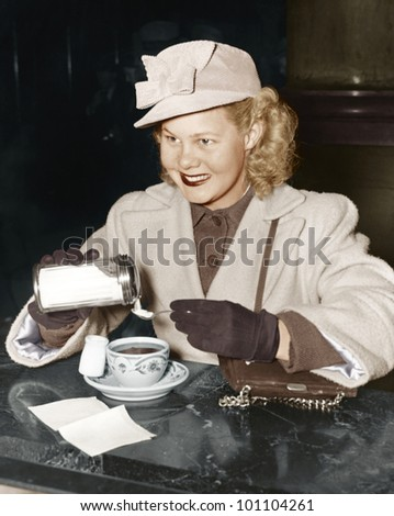 Woman adding sugar to beverage - stock photo