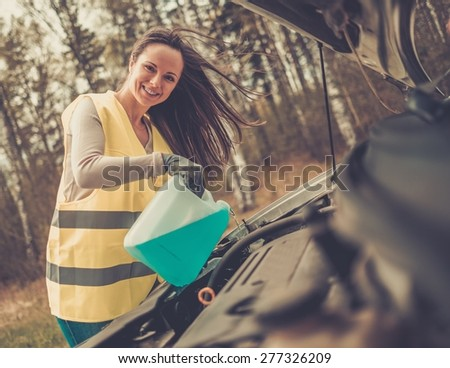 Woman adding washing fluid on a roadside - stock photo
