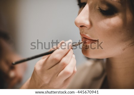 Woman adjusts lady's lips with a long thin brush