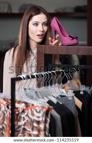 Woman admires excellent fuchsia shoes in the shopping mall - stock photo
