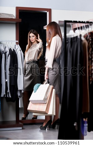 Woman admires herself at the mirror in the store after shopping - stock photo