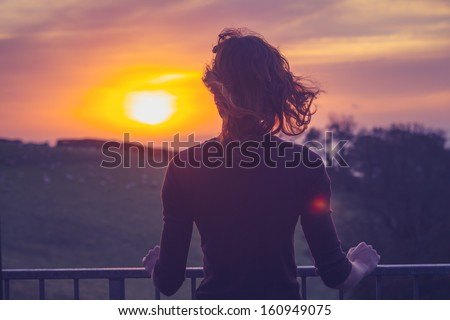 Woman admiring sunset from her balcony - stock photo