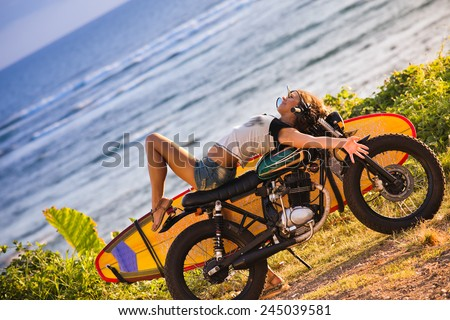 Woman adventure on motorcycle with surfboard at Bali - stock photo