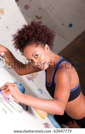 Woman (African-American) exercising at a climbing wall in a gym - stock photo