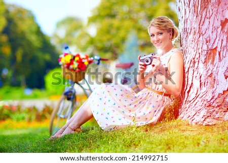 woman after bicycle ride relaxing with camera - stock photo