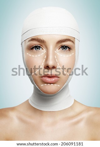 woman after plastic surgery with tied head and lines - stock photo