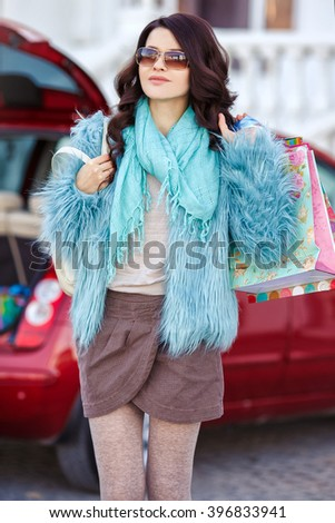 Woman after shopping in a mall or shopping centre and driving home now with her car. Smiling Caucasian woman putting her shopping bags into the car trunk. After shopping. car - stock photo
