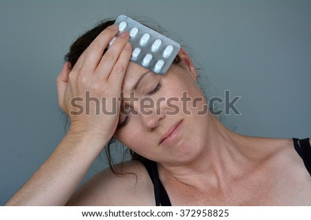 Woman (age 30-40) having headache taking pills. Helath concept