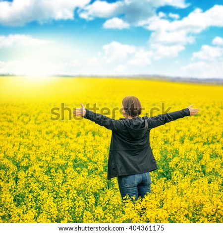 Woman agronomist standing in the field of blooming cultivated rapeseed and looking to  a distant point on the horizon.