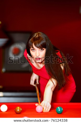Woman aiming for the billiard table in dark room