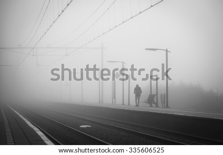 Woman alone at a train station, waiting for the train on a foggy day in autumn. - stock photo