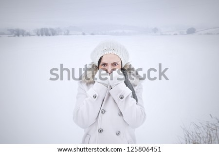 woman alone feeling cold in field covered in snow with copy space - stock photo