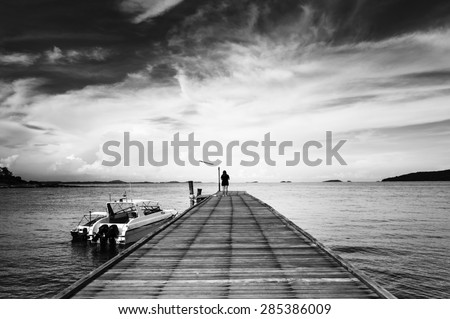 Woman alone on bridge to the ocean black and white style - stock photo