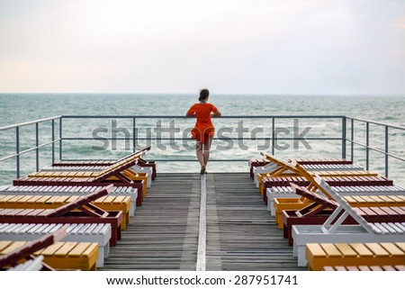 woman among the deck chairs on the pier in the sea - stock photo
