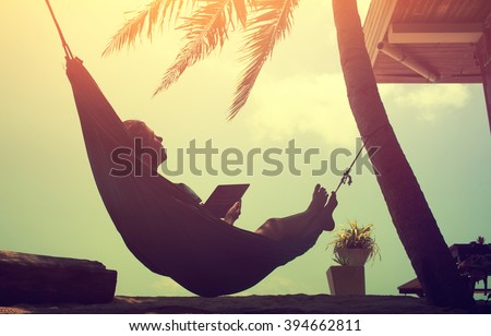 Woman an using a digital tablet computer while relaxing in a hammock