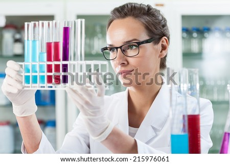 Woman analyzing test tubes with liquid, horizontal - stock photo
