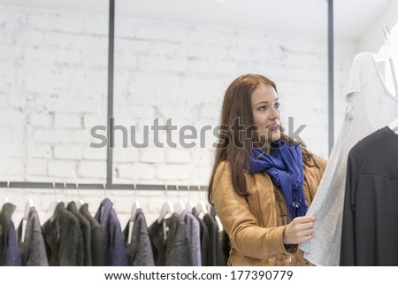 Woman analyzing top in store - stock photo