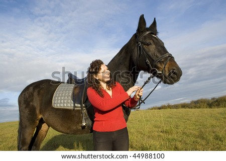 Woman and a horse standing in a field on the background of the cloudy sky.