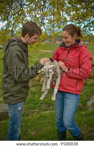 woman and a man taking care of a lamb