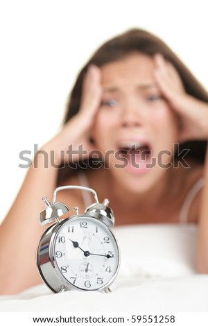 Woman and Alarm Clock. Funny image of woman lying in bed realizing she is late in the morning. Isolated on white background.