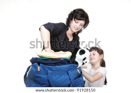 woman and baby daughter crammed full of clothes and blue shoulder bag isolated on white - stock photo