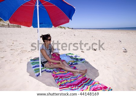 Woman and baby sitting under an umbrella at the beach - stock photo