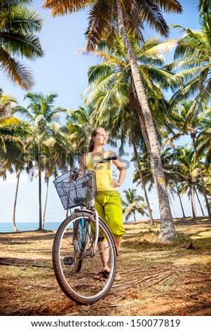 Woman and bicycle with basket on the beach near palm trees and ocean in India - stock photo
