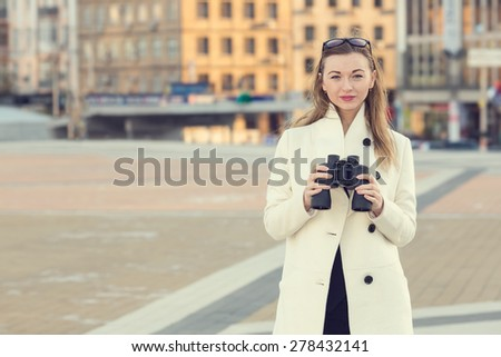 Woman and binoculars. Business woman with binoculars in his hand against the background of the streets downtown. Businesswoman holding binoculars. Concept - looking for a job. Young girl with spying. - stock photo