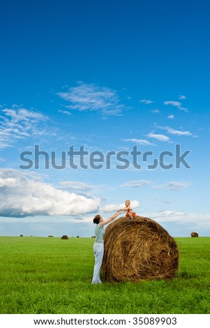 woman and boy in the field, boy sitting on hay stack - stock photo