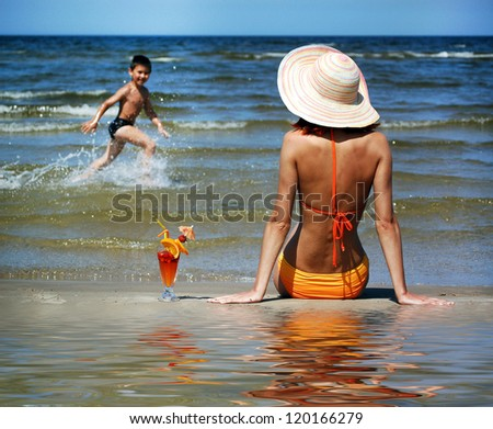 Woman and boy on the beach - stock photo