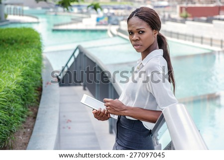 Woman and business. African businesswoman businessman standing near a fountain in downtown Dubai among the skyscrapers and looking at the tablet - stock photo