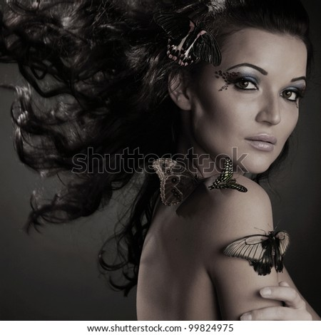 woman and butterfly on black - stock photo