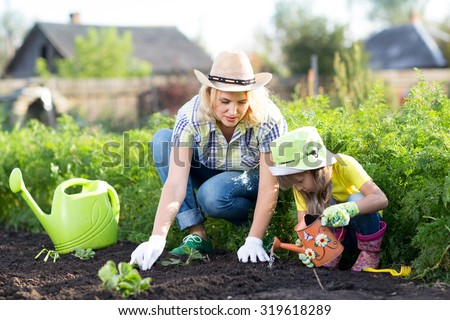 Woman and child girl, mother and daughter, gardening together planting strawberry plants in the garden