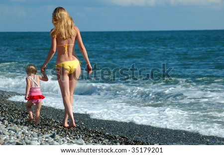Woman and child go on seaside