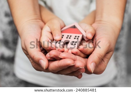 Woman and child hand hold house model. - stock photo