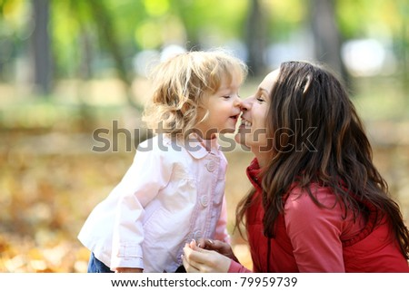 Woman and child having fun in autumn park