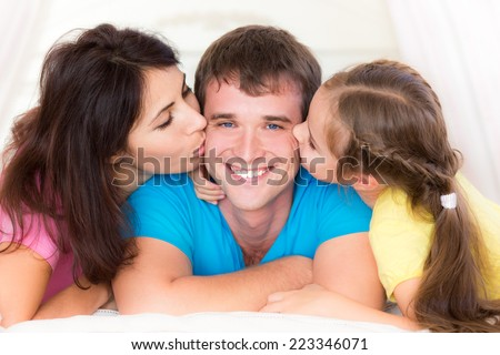 Woman and child kissing young man. Happy family having fun at home. Fathers day - stock photo