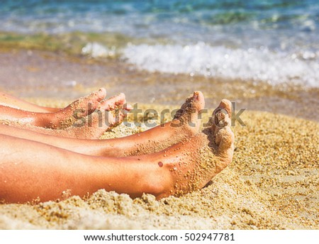 Woman and child legs on the sand beach, family summer lifestyle.
