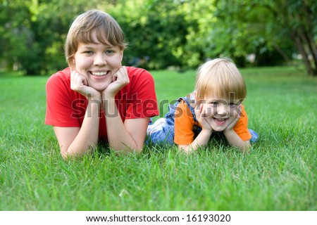 woman and child lie on green grass. Happy family
