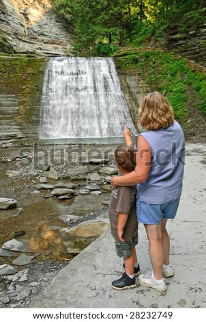 Woman and child looking at waterfall - stock photo
