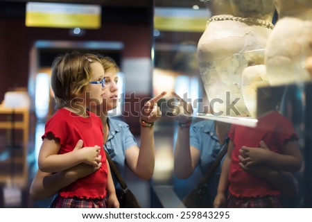 Woman and child looking old ancient amphora in historical museum - stock photo