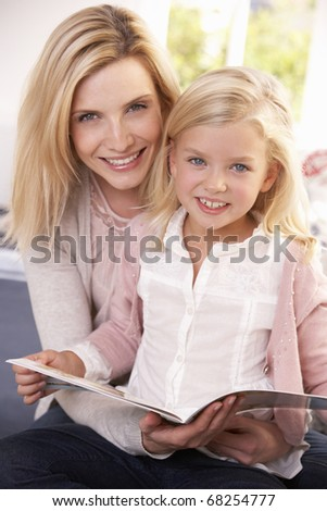 Woman and child reading together - stock photo