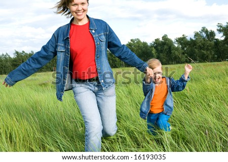 woman and child run on field. happy family - stock photo