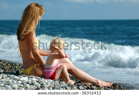 Woman and child sit on seaside