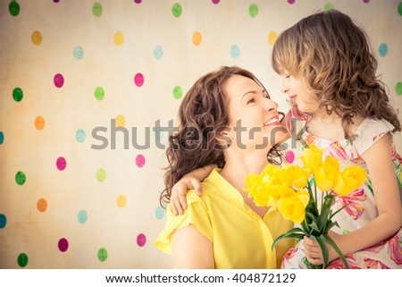 Woman and child with bouquet of flowers at home. Spring family holiday concept. Mother's day - stock photo