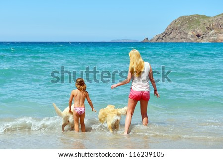 woman and child with dog playing in the sea