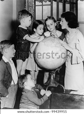 Woman and children looking at globe - stock photo